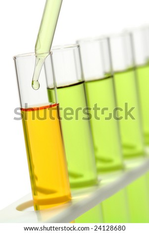 Laboratory pipette with drop of liquid inside test tube filled with orange liquid and other tubes full of green chemical solution on a rack for an experiment in a science research lab