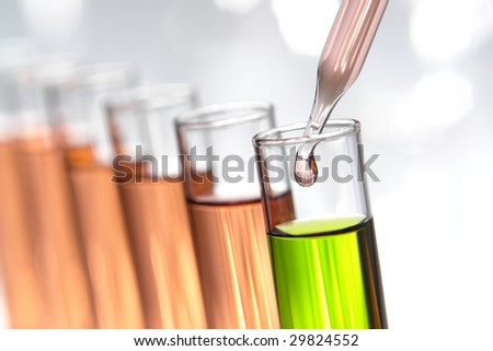 Laboratory pipette with drop of pink liquid over glass test tubes filled with green chemical solution for an experiment in a science research lab