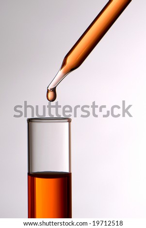 Laboratory pipette with drop of red liquid above test tube for an experiment in a science research lab