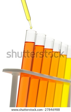 Laboratory pipette with drop of yellow liquid over glass test tubes filled with orange chemical solution for an experiment in a science research lab