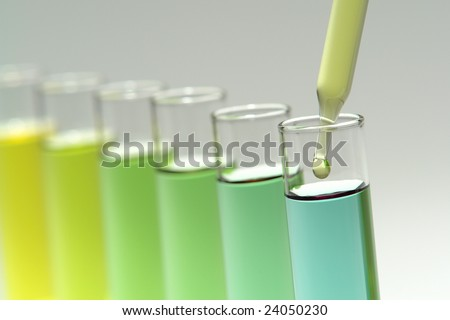 Laboratory pipette with drop of yellow liquid over glass test tubes for an experiment in a science research lab