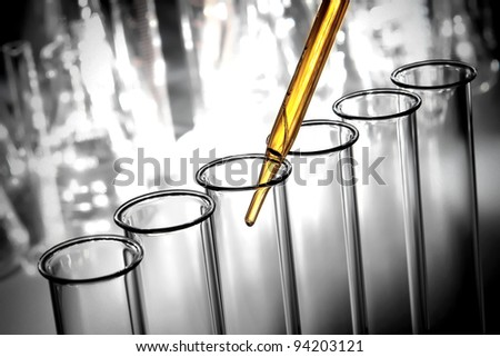 Laboratory pipette with emerging drop of yellow liquid over glass test tubes filled with chemical solution for a scientific experiment in a science research lab