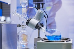 Laboratory rotary evaporator - homogenization process - rotating chemical flask for evaporate solvent from blue liquid at pharmacy factory or medical exhibition. Pharma, chemistry and science concept