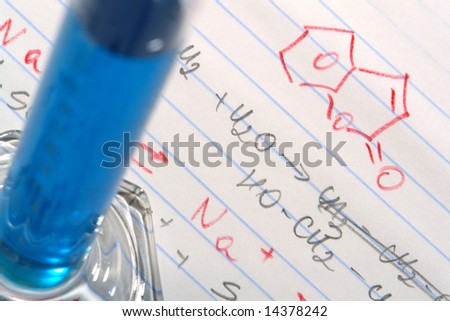 Laboratory scientific cylinder filled with blue liquid over note pad with hand written scientist chemistry formulas in a science research lab