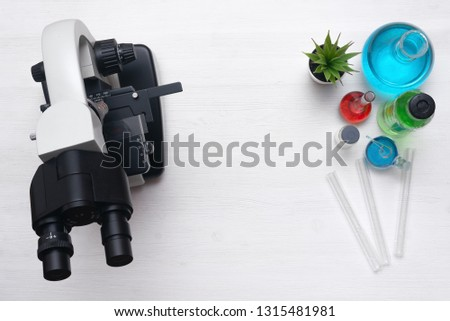 Laboratory table with a microscope and a chemical reagent liquids above. Chemistry or pharmacy background with copy space. Flat lay.