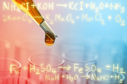 laboratory test tubes with gold chemical equation background
