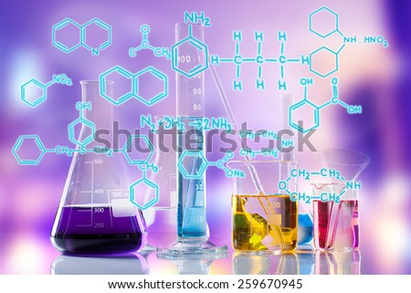 Laboratory tubes with colored liquids inside and formula on foreground