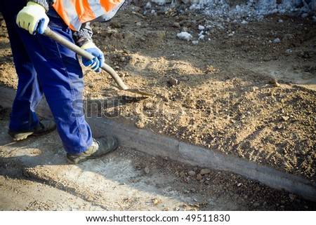 Laborer digging with shovel on construction site. Preparing for football European Cup 2012 in Poland.