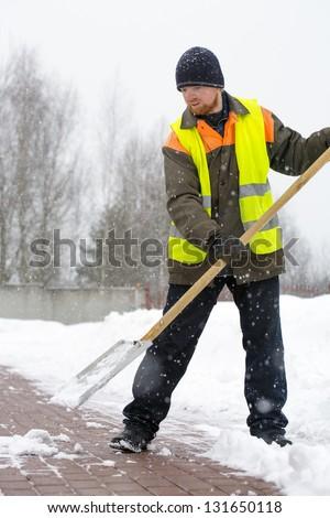 Laborer man road worker in uniform and reflective vest shoveling snow