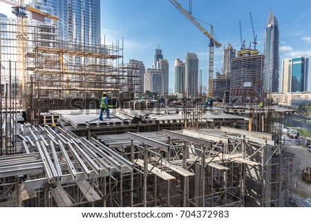 Laborers working on modern constraction site works in Dubai. Fast urban development consept. stock photo