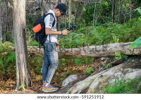 Labuan,Malaysia-Feb 12,2017:Videographer holds DJI Osmo Handheld 4K camera during hiking in Pancur Hitam hill in Labuan,Malaysia.It is a handheld 4K camera that uses 3-axis gimbaled stabilisation #591251912