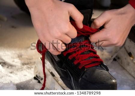 Lace up hockey skates. Laces on hockey skates.Tie hockey skates.Tie shoelaces on hockey skates. #1348789298