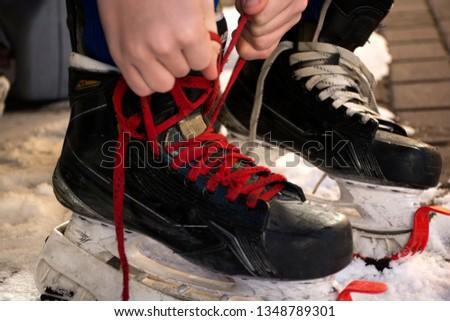 Lace up hockey skates. Laces on hockey skates.Tie hockey skates.Tie shoelaces on hockey skates. #1348789301
