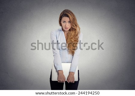 Lack of confidence. Insecure worried young woman holding laptop feels awkward isolated grey wall background. Human face expression emotion body language life perception
