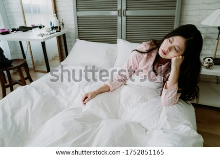 lack of energy asian woman feel miserable and doesn't want to get out bed. japanese female sitting in bed is propping her head, lost in daze. Photo stock ©