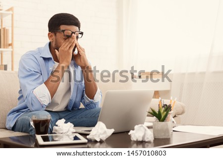 Lack of ideas. Tired african-american man working at home, can't make financial or annual report, copy space