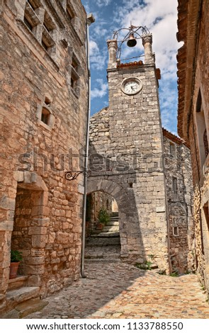 Lacoste, Vaucluse, Provence, France: the bell and clock tower in the old town of the picturesque medieval village