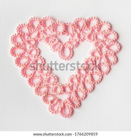 Lacy soft pink heart woven using the tatting technique on a light background. Weaving lace tatting is a kind of elite needlework. Photo stock ©