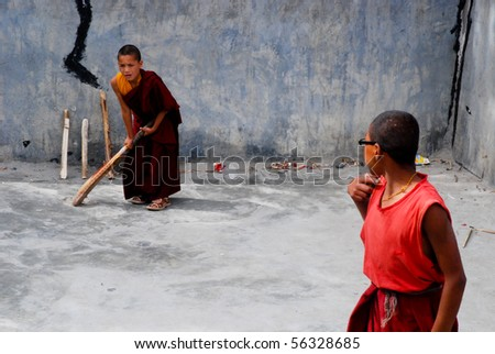 LADAKH, INDIA - CIRCA JULY 2009: Two young buddhist monks playing India's most popular sport, cricket circa July 2009 in Ladakh, India.