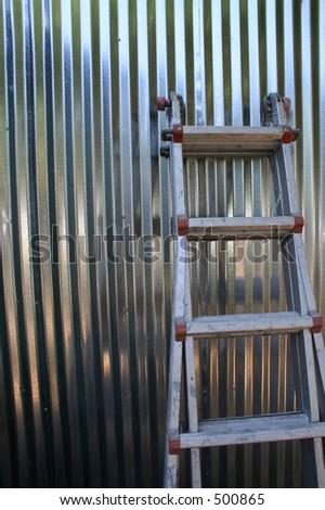 Ladder Against Shiny Silver Corrugated Aluminum Siding Wall