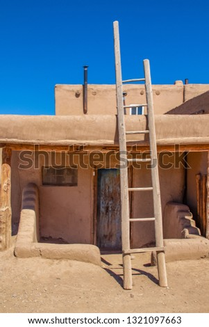 Ladder leading to second story apartments on traditional mud adobe pueblo with porch and old grunge wooden door in American southwest