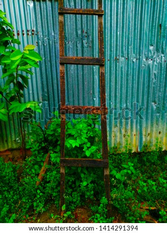 Ladder leaning on a store room made of tin.
