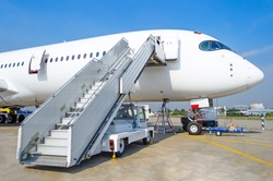 Ladder to the entrance of the aircraft in the parking lot at the airport, view the nose of the aircraft