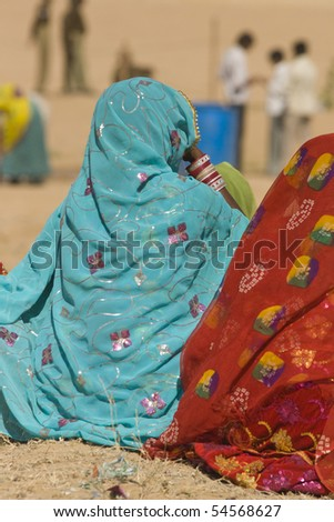 Ladies in brightly colored saris sitting on the ground watching events at the Desert Festival in Jaisalmer, Rajasthan, India