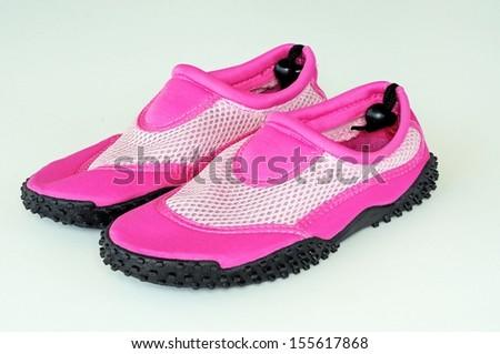 Ladies pink beach shoes against a plain background.