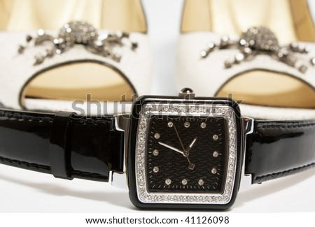 Ladies' watch and high heels shoes on white