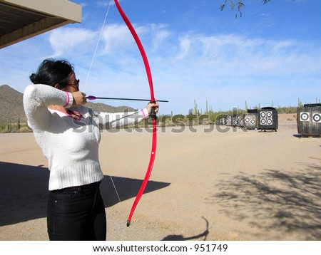 Lady at archery range shooting targets
