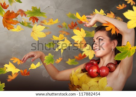 Lady Autumn in swirling falling leaves