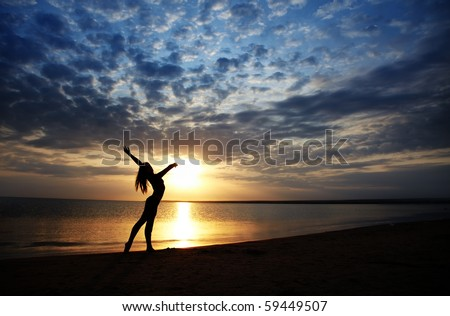 Lady doing exercise at the beach during sunset. Vivid colors and natural darkness