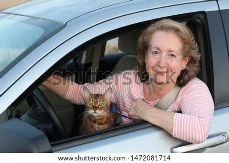 Lady driving with her feline companion #1472081714