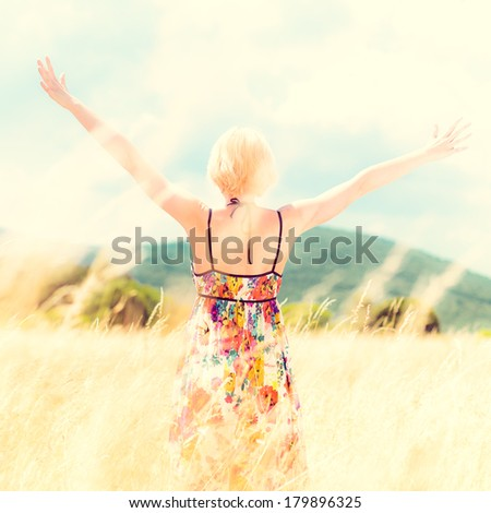 Lady enjoying the nature. Young woman arms raised enjoying the fresh air in summer meadow. Instagram style retro shot.