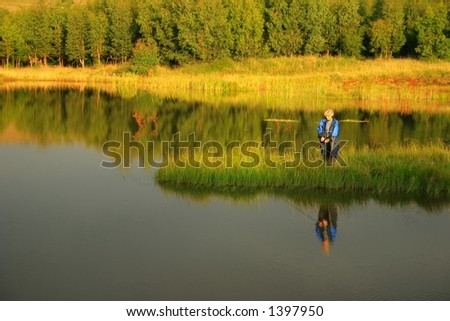 Lady fly fishing, calm water, late afternoon