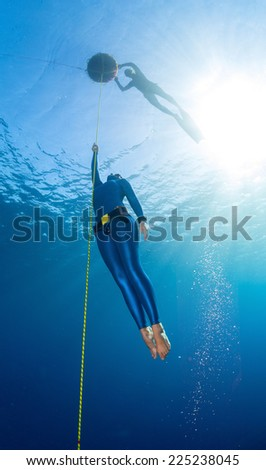 Lady free diver ascending along the rope linked to the buoy on surface. Free immersion discipline