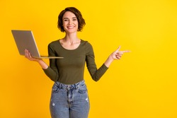 Lady hold laptop point finger empty space advertisement promo recommendation concept isolated on shine yellow color background