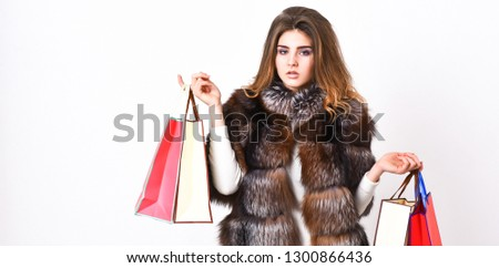 Lady hold shopping bags. Discount and sale. Fashionista buy clothes on black friday. Girl makeup furry coat shopping white background. Shopping or birthday gifts. Woman shopping luxury boutique.