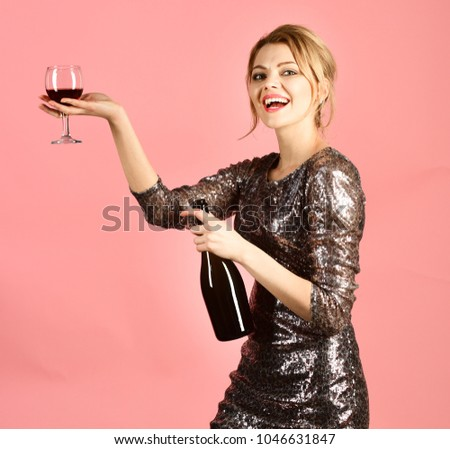 Lady holding glass and bottle of red Italian wine. Girl with smiling face drinks expensive cabernet or merlot. Winetasting concept. Woman in shining dress with alcohol on pink background. #1046631847