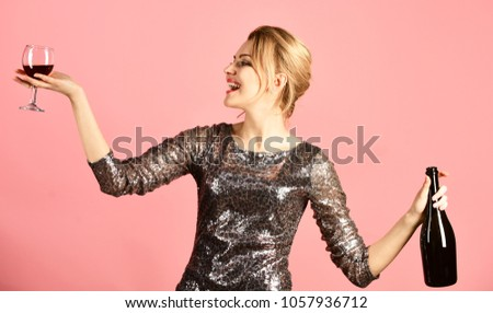 Lady holding glass and bottle of red Italian wine. Winetasting concept. Girl in shining dress with alcohol on pink background. Woman with smiling face drinks expensive cabernet or merlot. #1057936712