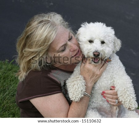 Lady holding her adorable white puppy