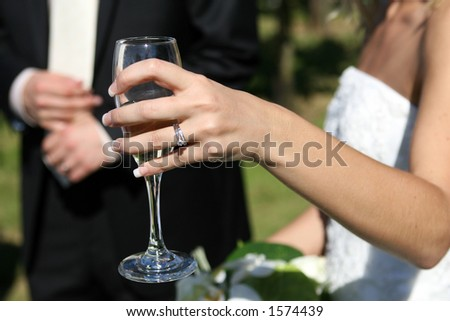 Lady in a white dress holds a glass at a function