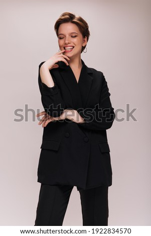 Lady in black suit happily posing on white background. Cheerful woman in dark jacket and pants smiling on isolated Stock photo ©