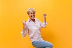 Lady in good mood rejoices on orange background