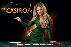 Lady in green dress is showing inscription casino, leaning on playing table with cards on it, posing on black background. Poker, casino. Copy space