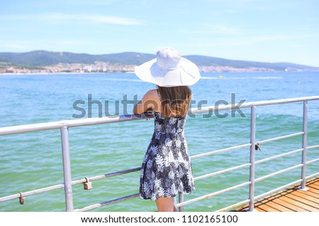 Lady in hat on the pier of Sunny Beach #1102165100