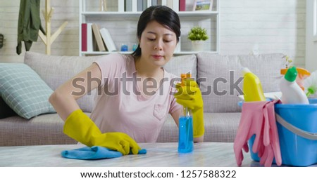 lady in protective gloves doing housework in the living room in the daytime. young asian woman casual lifestyle concept at home. girl housekeeper using rag cleaning up wiping the marble table. #1257588322