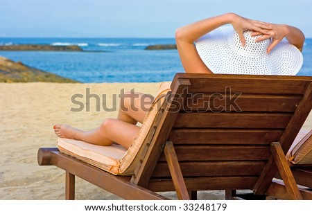 Lady in white hat sitting in chaise longue