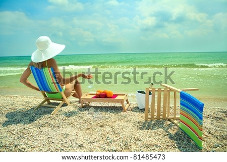 Lady in white hat sitting in chaise longue with glass of champagne